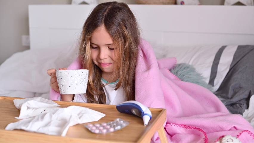 The child is sick, drinks tea and sneezes, covers his face with a napkin. A little girl is sitting on the bed, she has a cold. The concept of viral and seasonal diseases COVID 19. 4k footage