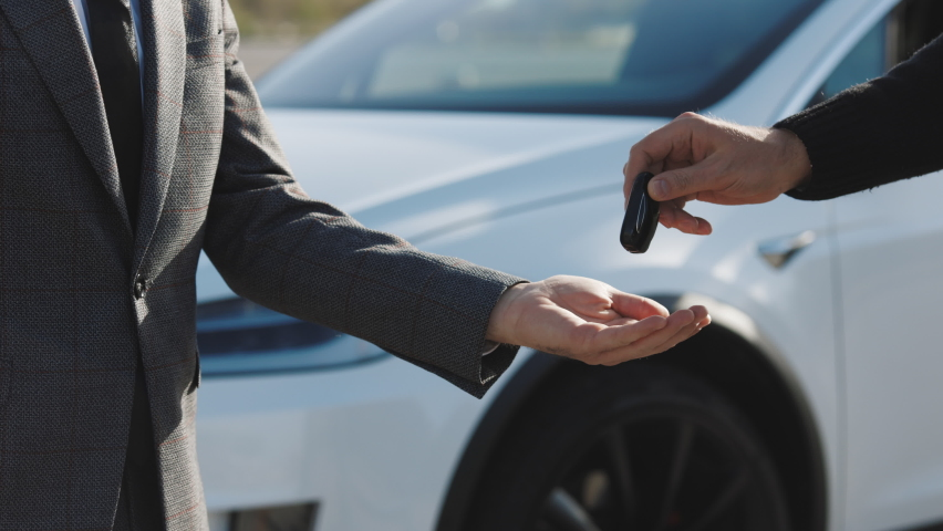 Male hand gives a car keys to male hand in the car dealership close up. Unrecognized auto seller and a man who bought a vehicle shake hands. Dealer giving key to new owner in auto show or salon. | Shutterstock HD Video #1061468422