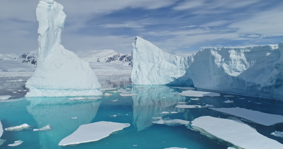 Tabular icebergs melt at turquoise ocean bay. Huge high ice glacier at polar nature environment. Arctic winter landscape at global warming problem. Desert white land of snow and ice drone shot. Royalty-Free Stock Footage #1061470264