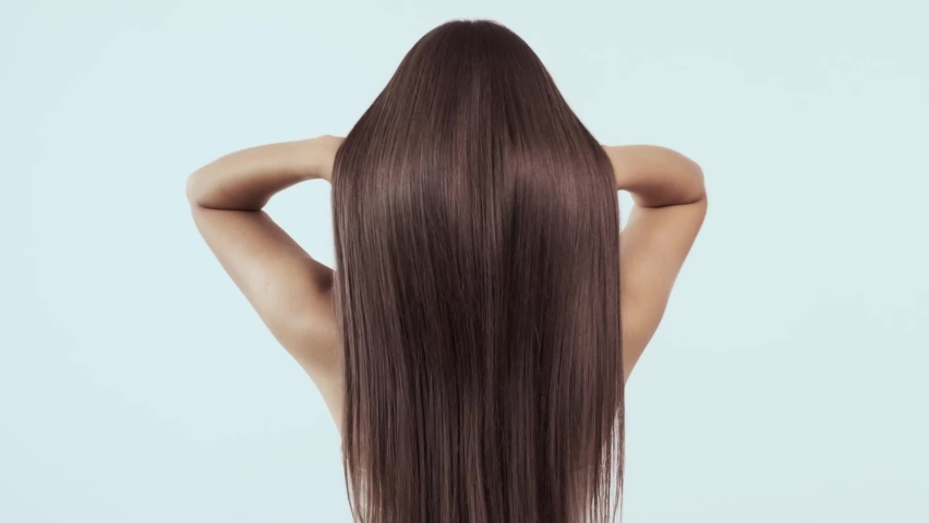 Woman moves long hair. Rear view. Girl shakes long straight hair. Female model is fluttering hair.   Slow motion footage. Rear view. Ginger. Red haired. Royalty-Free Stock Footage #1061470717