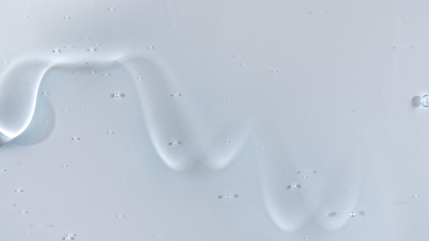Transparent cosmetic gel fluid flowing down on a white surface. Macro Shot