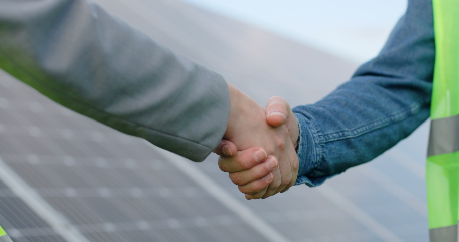 Close up of handshake on solar panel background outside. Female engineer shakes hands with partner in agreement.