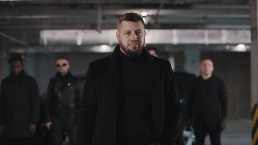 Medium footage of tall bearded caucasian bandit holding handgun looking at camera chewing gum and his squad in black jackets and sunglasses standing behind at underground parking | Shutterstock HD Video #1061474113