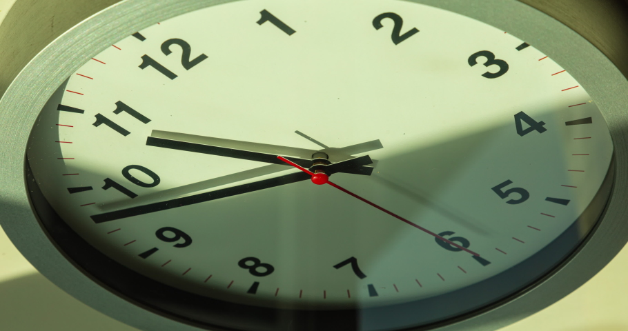Time lapse on a analog wall clock, 12 hours, from the morning to afternoon. The time pointer moving slow while the seconds pointer running fast. Sun and sky reflecting in the surface of the watch.  | Shutterstock HD Video #1061475937