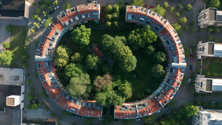 Aerial top down view of circle shaped buildings, raising above the houses | Shutterstock HD Video #1061476438