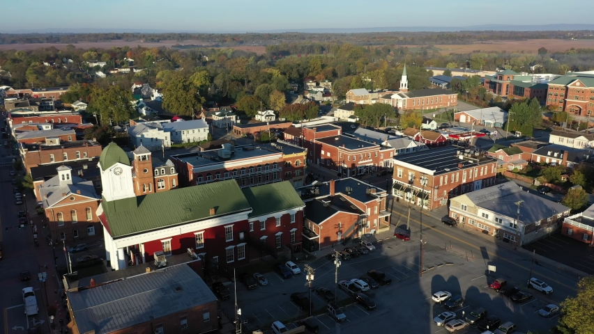 Aerial descending shot showing Charles Town courthouse, Ranson, WV, and university buildings in autumn in the early morning.