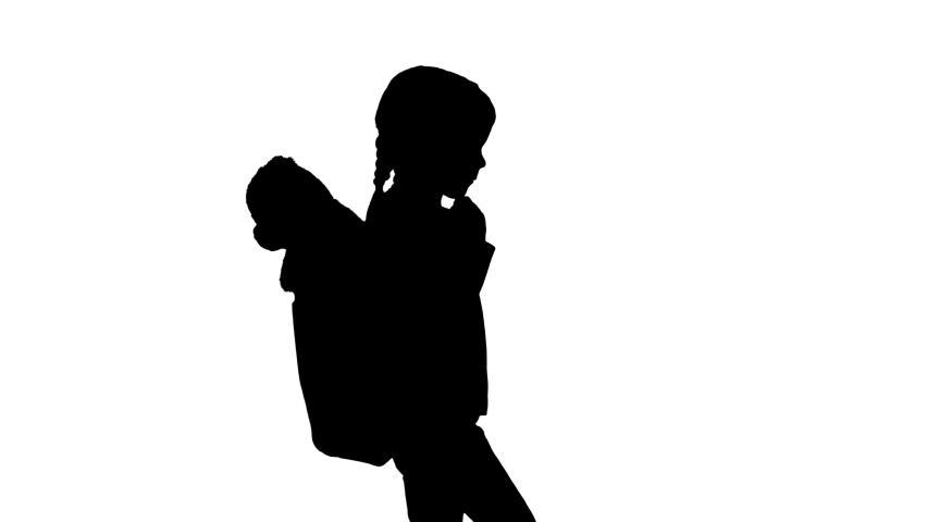Silhouette Cute little girl walking to school with a teddy bear sticking out of her backpack.