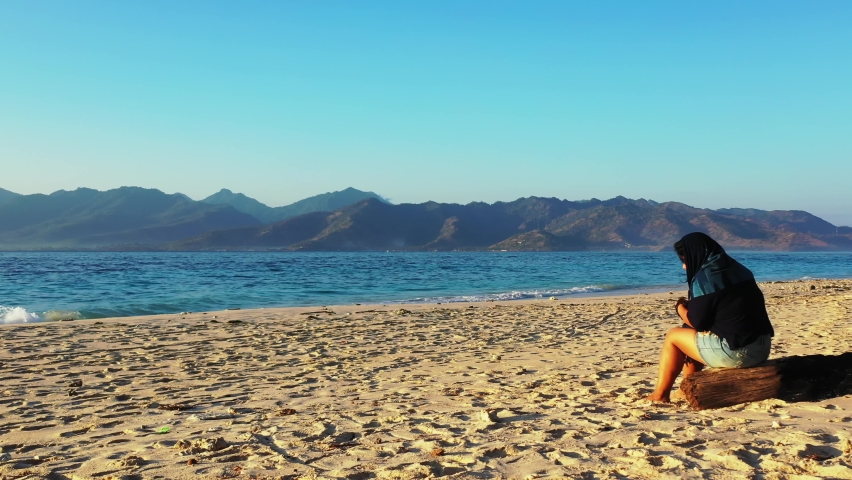 Wide angle of an Asian woman fixing her shawl above her head as she sits on a wooden log at the beach and watching the waving sea nearby the tall mountains, slowly tracking forward. | Shutterstock HD Video #1061488762