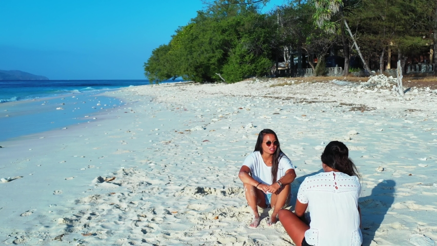 Wide angle of two girls in white summer clothes talking as they relax together on the beach with a tall forest nearby the waving blue sea during a bright sunny day, slowly tracking backwards. | Shutterstock HD Video #1061488813