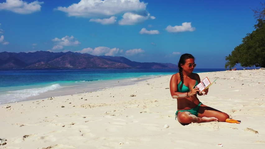 Wide angle of a pretty Asian girl reading a travel catalog as she enjoys sunbathing on the white sand beach with tall trees nearby the waving blue sea during daytime, slowly zooming in. | Shutterstock HD Video #1061488855