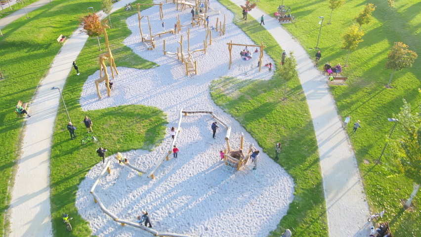 Aerial angle of a park full of tall trees and grass with a playground where families bond and have fun together on a calm sunny day, tracking forward. | Shutterstock HD Video #1061488885