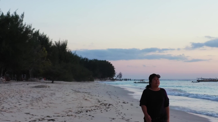 Asian woman walking slowly on a white sand beach with a tall forest and seashells nearby the waving sea during a calm afternoon, tracking backwards. | Shutterstock HD Video #1061488969