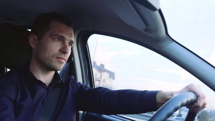 Young man inside car. Businessman driving transport alone careful. Look forward and to side. Handsome driver in car. Royalty-Free Stock Footage #1061493070