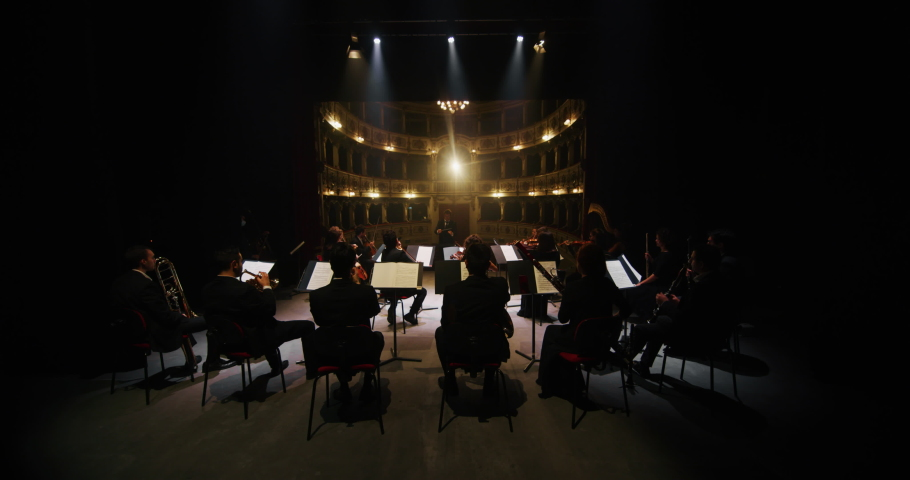 Cinematic shot of conductor directing symphony orchestra with performers playing violins, cello and trumpet on classic theatre with curtain stage during music concert with dramatic lights.