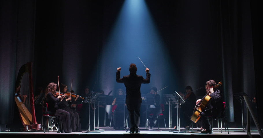 Cinematic shot of conductor directing symphony orchestra with performers playing violins, cello and trumpet on classic theatre with curtain stage during music concert with dramatic lights. Royalty-Free Stock Footage #1061499877