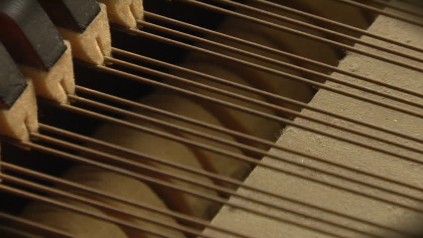 close up shot of the inner workings of a grand piano.  The hammers strike the strings as the shot slowly zooms out.