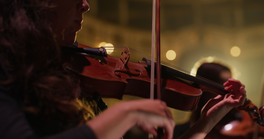 Cinematic close-up shot of female violinist is playing violins during musical concert on classic theatre stage with symphony orchestra performing on background. Royalty-Free Stock Footage #1061500504
