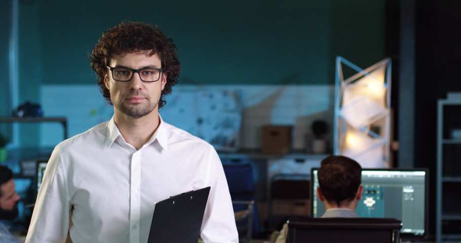 Portrait of sales manager in white shirt with glasses standing in the middle of the office with folder in his hands and smiling. | Shutterstock HD Video #1061503729