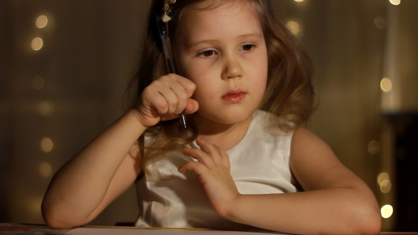 Child invents idea and writing a letter in roomat night. Portrait caucasian baby girl close up thinks in the light of lights.