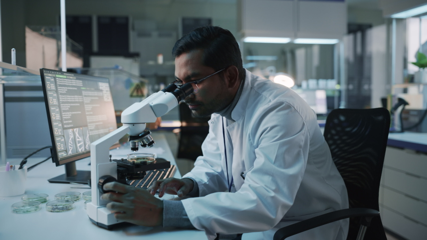Medical Research Scientist Conducts DNA Experiments Under a Microscope and Writes Results on Desktop Computer in a Biological Science Laboratory. Diverse Multiethnic Lab with Engineers in White Coats. Royalty-Free Stock Footage #1061506315