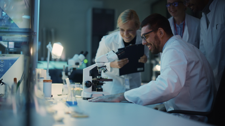 Surprized Male Reseach Scientist Makes an Important Discovery While Researching Samples Under the Microscope. Happy Colleagues Give High Five and Share Success with Fellow Bioengineers. Royalty-Free Stock Footage #1061506336