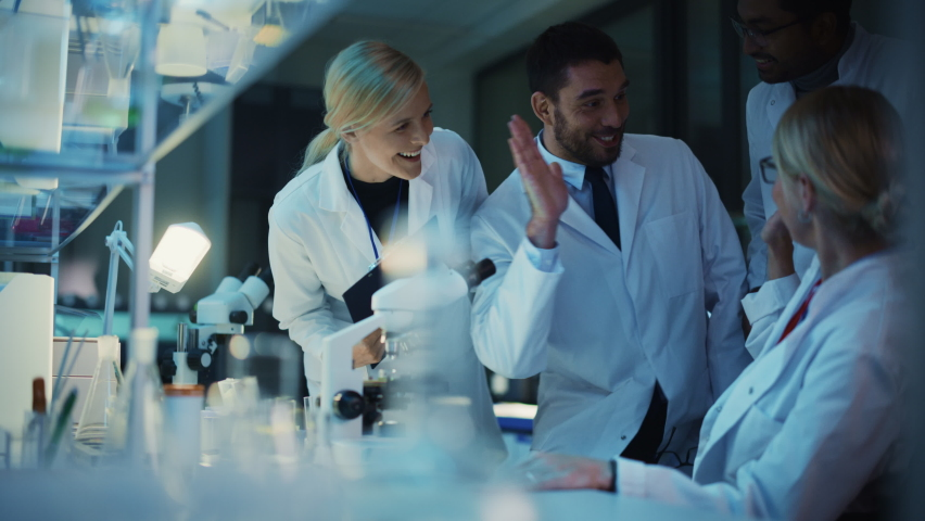 Surprized Female Reseach Scientist Makes an Important Discovery While Researching Samples Under the Microscope. Happy Colleagues Give High Five and Share Success with Fellow Bioengineers. Royalty-Free Stock Footage #1061506339