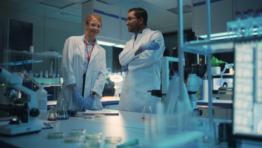 Female and Male Medical Research Scientists Have Conversation and Use Futuristic Virtual Technological Interface in a Modern Science Laboratory. Space for Augmented Reality Hologram is Left Empty. | Shutterstock HD Video #1061506396
