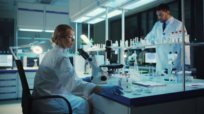 Medical Research Scientist Looks at Biological Samples Under Digital Microscope in Applied Science Laboratory. Beautiful Caucasian Lab Engineer in White Coat Working on Vaccine and Medicine.