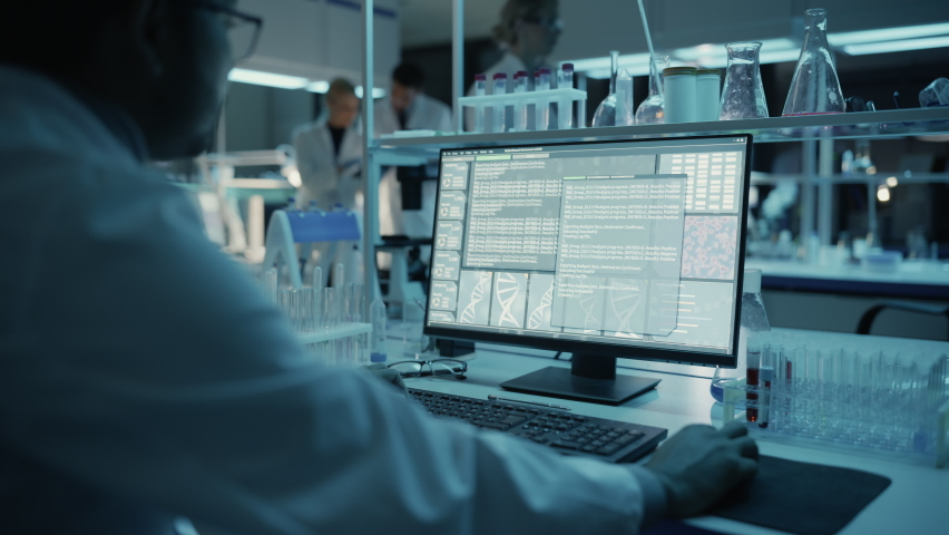 Medical Research Scientist Typing Sophisticated Coding on His Desktop Computer in a Biological Applied Science Research Laboratory. Lab Engineers in White Coats Conduct Experiments in the Background. Royalty-Free Stock Footage #1061506423