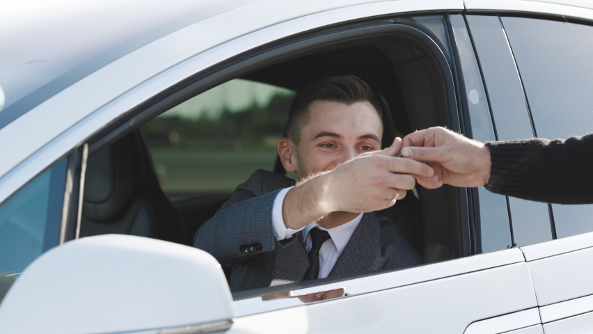 Car Salesman Finishing Up Dealing Car. Young Happy Man Receiving Car Keys to Her New Automobile. Dealer giving key to new owner in auto show or salon.