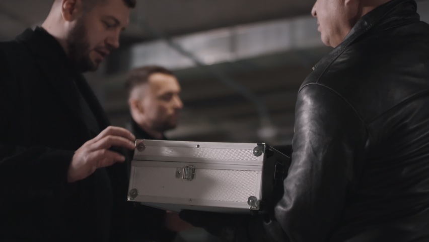 Closeup of multi ethnic bandits checking briefcase with money making illegal business deal at underground parking | Shutterstock HD Video #1061510308