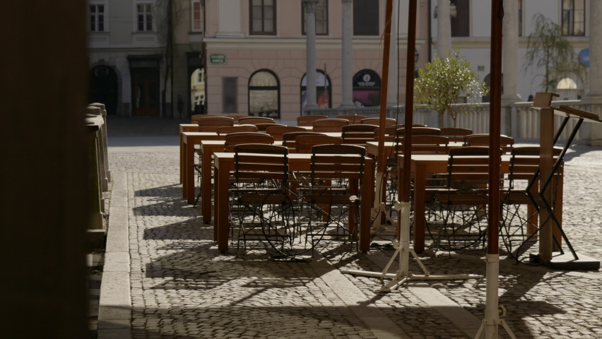 Empty bar tables and chairs closed as a result of a coronavirus quarantine. Bars and restaurants in Ljubljana are closed due to covid-19 epidemic. Royalty-Free Stock Footage #1061510785