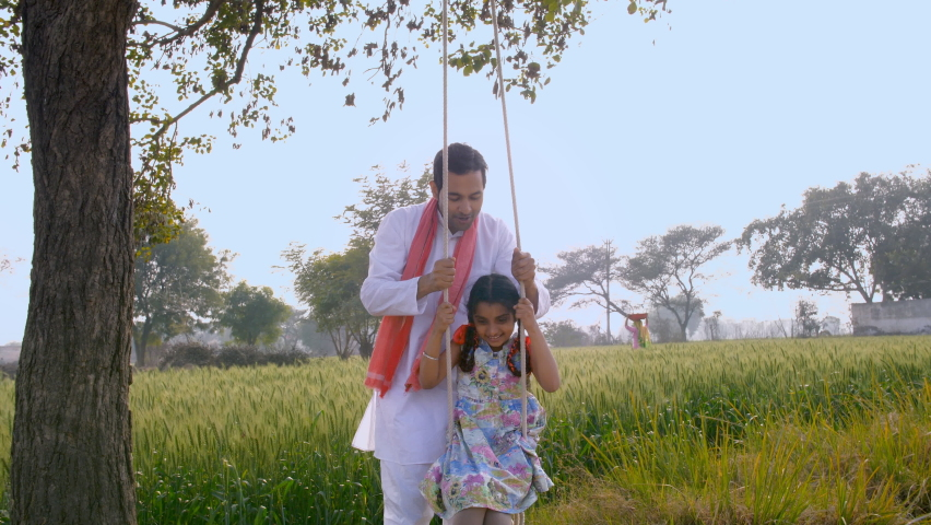 Cute little girl happily playing with her father on a tree swing during leisure time. Indian farmer spending quality time with his daughter in their agricultural field - happy family, parenting Royalty-Free Stock Footage #1061511034