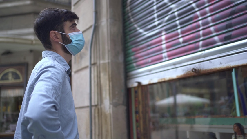 Young business man with mask closing a small local store door during the coronavirus crisis  Royalty-Free Stock Footage #1061517004
