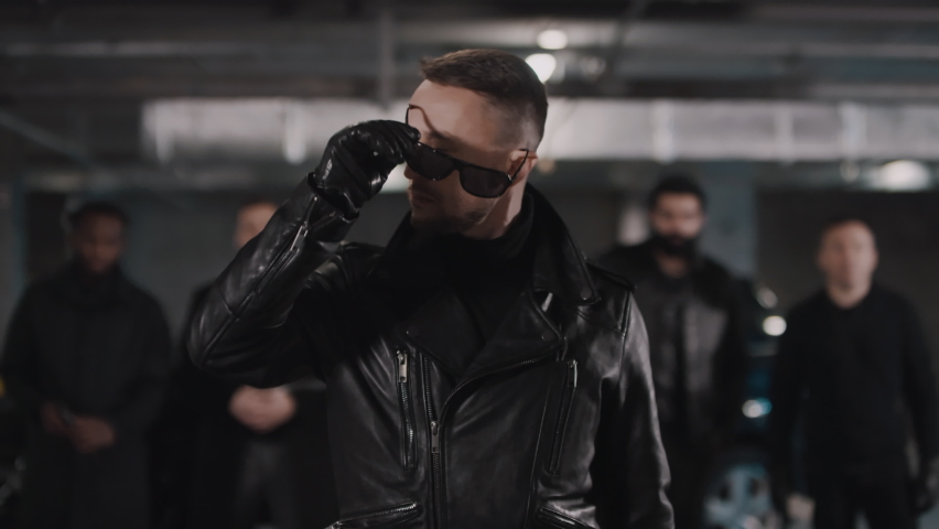 Portrait of brutal caucasian bearded mobster in leather gloves and jacket taking off black sunglasses looking seriously at camera with gang standing in background | Shutterstock HD Video #1061517568