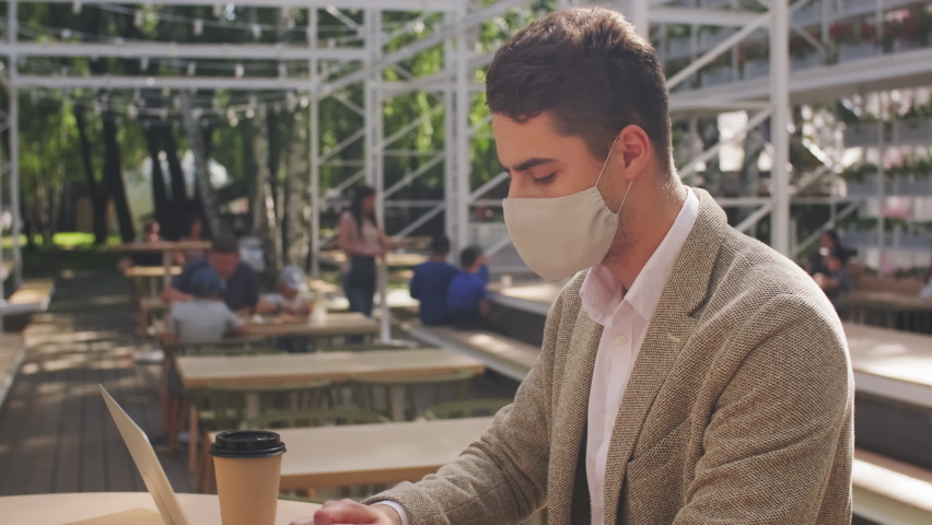 Slowmo tilt down of busy businessman in face mask sitting at table in outdoor patio of cafe and typing on laptop | Shutterstock HD Video #1061518261