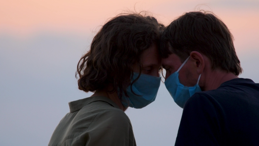 Couple in protective masks. Tender moment family support, forgive and understanding during Covid-19, Coronavirus pandemic. Young couple in mask support each other. Man and woman in medical face mask Royalty-Free Stock Footage #1061518621