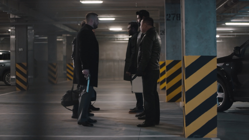 Over-the-columns full shot of two multi ethnic criminal squads going in different directions at underground parking after finishing deal by transmitting of money | Shutterstock HD Video #1061519095