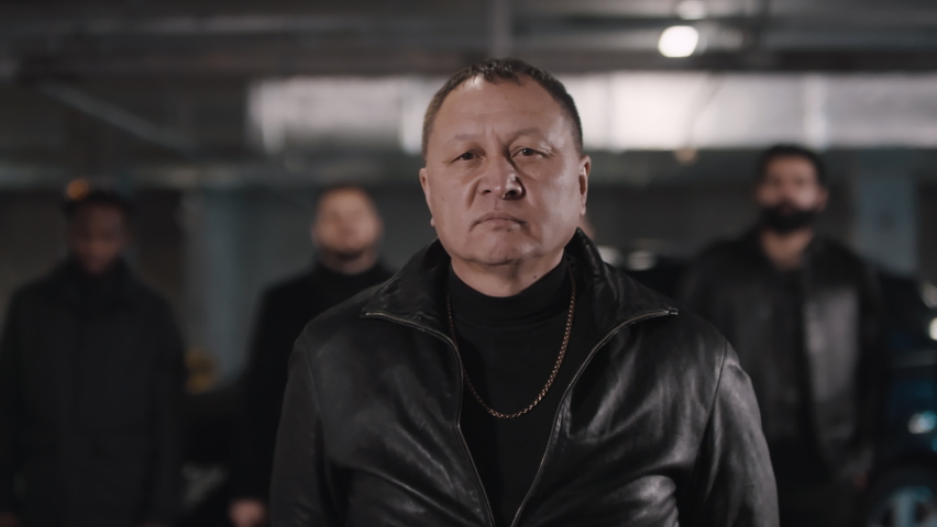 Medium closeup of assertive Asian gangster leader looking at camera ahead his armed with handguns multi ethnic gang at isolated underground parking | Shutterstock HD Video #1061520079