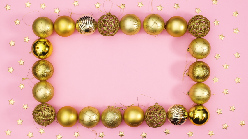 6k Gold Christmas ornament balls make frame with empty space inside and gold stars around on pink theme. Stop motion  | Shutterstock HD Video #1061521039