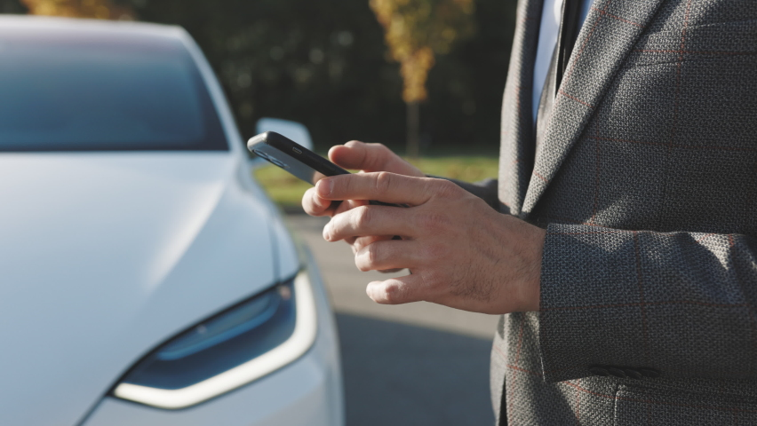 Businessman controls a self-driving electric car using mobile application. Autonomous autopilot driverless car. Smartphone app. Sensor scanning road ahead for vehicles, danger, speed limits Royalty-Free Stock Footage #1061524258