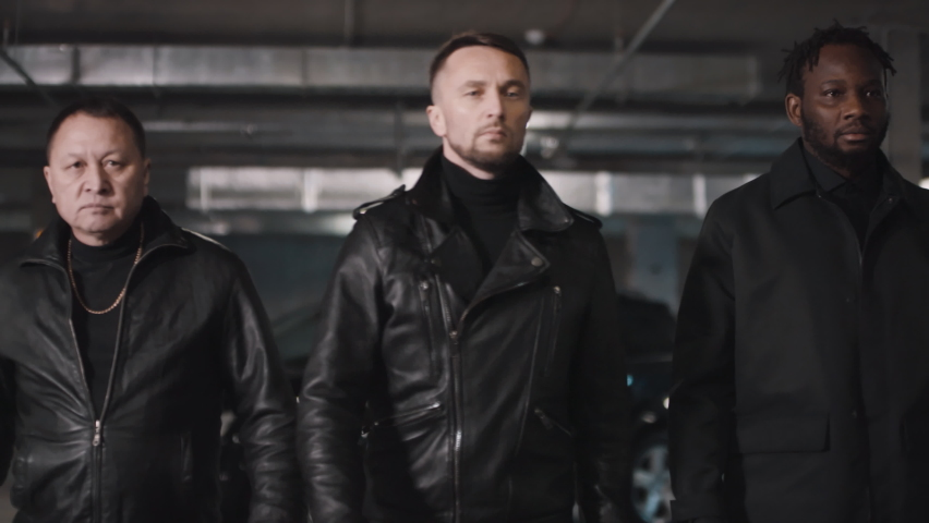 Medium slowmo footage of brutal Caucasian, African American and Asian mobsters in leather jackets walking towards camera in dark underground parking | Shutterstock HD Video #1061525983