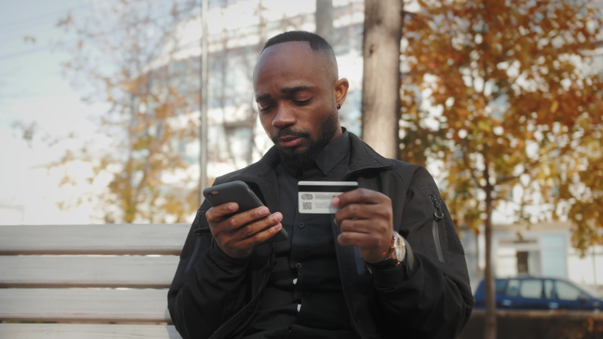 Smiling customer holding credit card and smartphone sitting on bench in the park. Happy african american man shopper using instant easy mobile payments making purchase in online store. Royalty-Free Stock Footage #1061528332