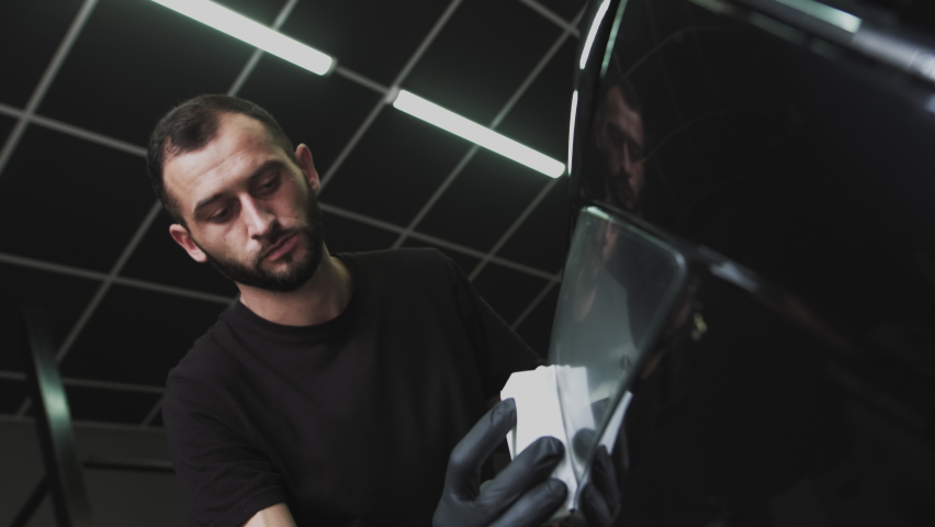 Applying protection for headlights. Professional Car Ceramics Worker applies a layer of ceramics protective rain cover on car windows. Concept from Nano Protection, Different accessories, Long | Shutterstock HD Video #1061528683