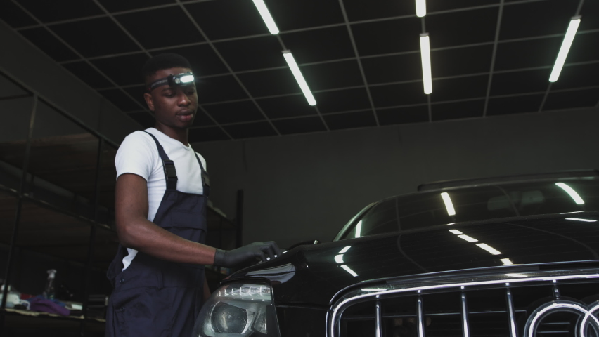 An African-American service worker applies a protective layer.Headlight Polishing, processing of car lights. A car service worker polishes the headlight of a passenger car. Professional polishing. | Shutterstock HD Video #1061528686