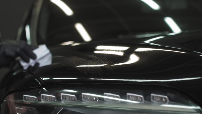 Car detailing - Man applies nano protective coating or wax on black car. Covering car bonnet with a liquid glass polish | Shutterstock HD Video #1061528689