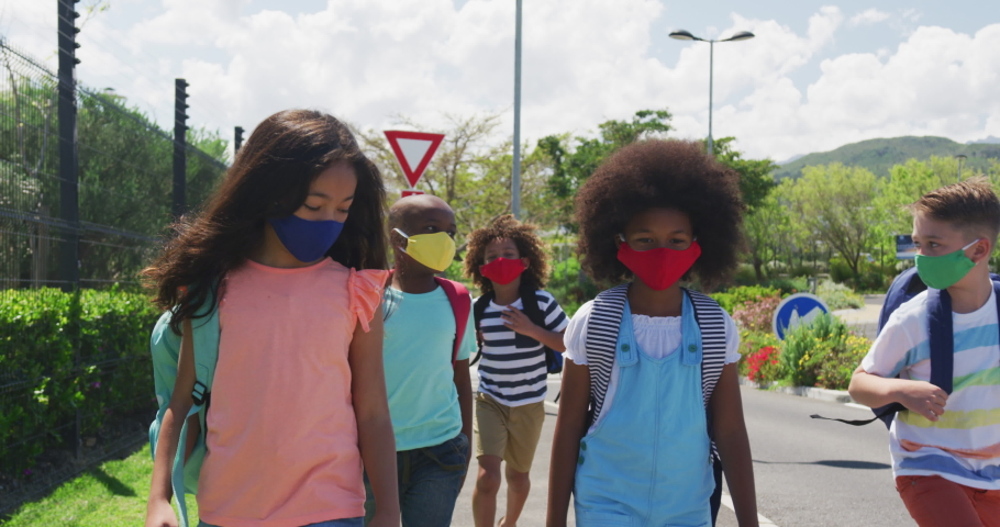 Multi ethnic group of school children wearing face masks, walking on a street. Education back to school health safety during Covid19 Coronavirus pandemic Royalty-Free Stock Footage #1061532817