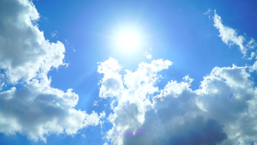 Low Angle view TimeLapse of direct bright noon sun on blue sky with clouds,sun shining on  summer hozizon in vibrant sunlight,sunbeam & sun ray flares with white cumulus clouds at midday sunshine day