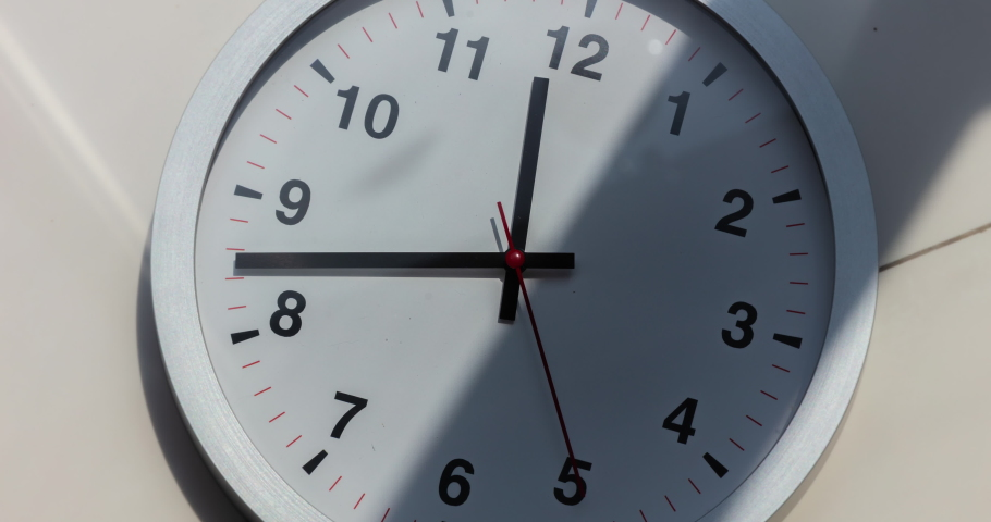Wall clock show the running time. Time lapse on a modern wall clock.  Close up to a wall clock, with running time pointer. Sun and sky reflecting in the watch during the time passing by | Shutterstock HD Video #1061535892