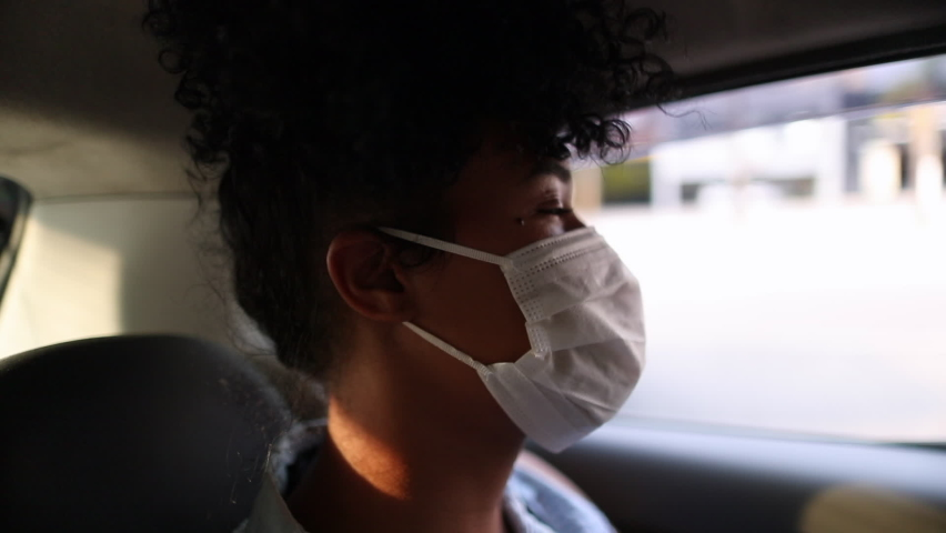 Passenger wearing surgical mask riding taxi during pandemic, black african american woman looking out car window. | Shutterstock HD Video #1061536573